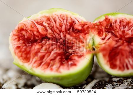 Fresh fig with red juicy fruit flesh and green skin cut in at halves on grey background