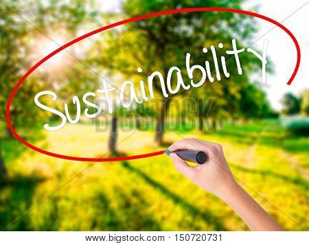 Woman Hand Writing Sustainability  With A Marker Over Transparent Board