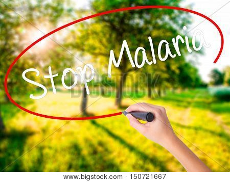 Woman Hand Writing Stop Malaria  With A Marker Over Transparent Board