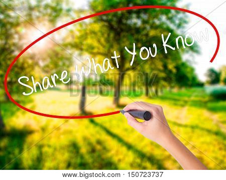 Woman Hand Writing Share What You Know With A Marker Over Transparent Board
