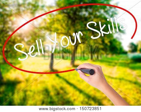 Woman Hand Writing Sell Your Skills With A Marker Over Transparent Board