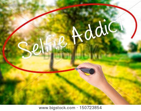 Woman Hand Writing Selfie Addict With A Marker Over Transparent Board