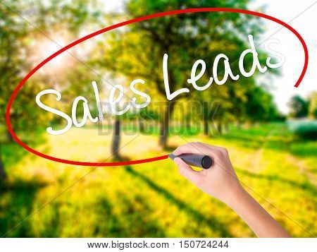 Woman Hand Writing Sales Leads With A Marker Over Transparent Board