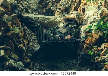 Soldier in the barricade with the gun. Bearded man in camouflage suffers in the pile of bricks