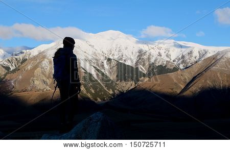 A Woman Hiker Looking to The Snowy Southern Alps.  Castle Hill, Canterbury, New Zealand.
