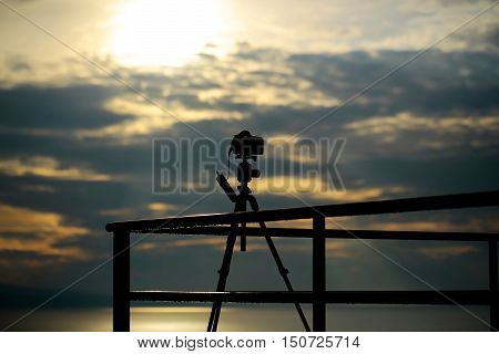 Photo camera on tripod dark silhouette at viewpoint on cloudy sky over sea on evening