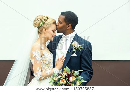 Young Groom Kisses Beautiful Bride