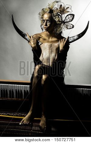 pretty golden woman or girl has makeup and body art metallized color with decorative flowers holding animal skull with antlers or horns sitting on old wooden piano with keyboard on grey background