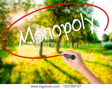 Woman Hand Writing Monopoly With A Marker Over Transparent Board .
