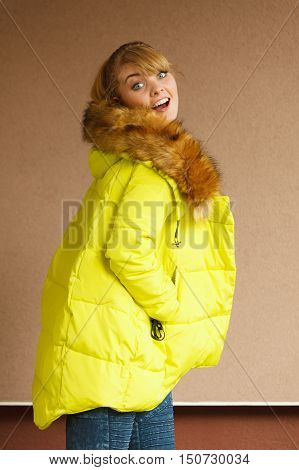 Beautiful smiling young fashionable girl wearing opened jacket with hood. Fashion in winter time.