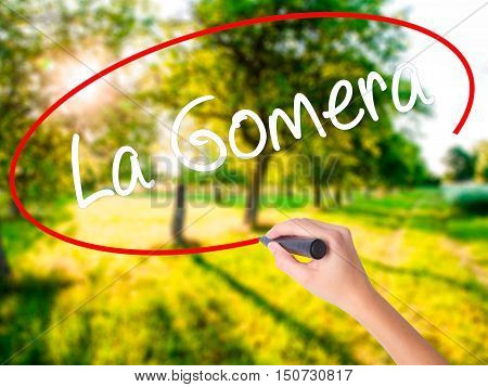 Woman Hand Writing La Gomera With A Marker Over Transparent Board .