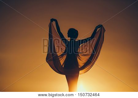 Silhouette of slim girl young woman female model dances in transparent windy dress on nature over beautiful sunset
