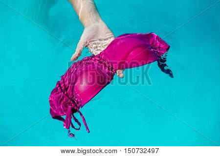 hand with wet female swimsuit bra or brassiere pink color floating in blue water of swimming pool with nobody