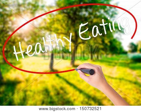 Woman Hand Writing Healthy Eating With A Marker Over Transparent Board