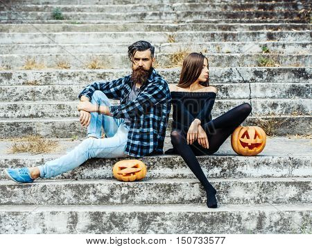 young halloween couple of bearded man with beard and mustache and girl in black tights sit on stony stairs with traditional autumn holiday symbol of orange spooky pumpkin outdoor