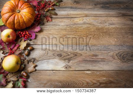 Thanksgiving or fall greeting with pumpkins and fall leaves on blue background. Fall background. Thanksgiving background with seasonal vegetables and fruits. Copy space