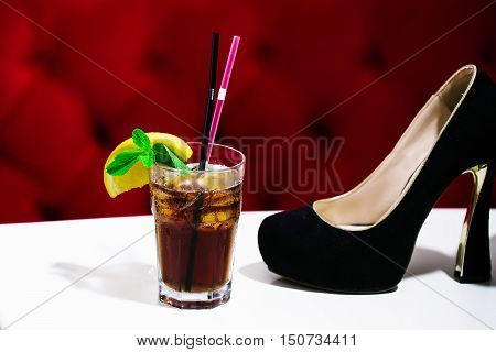 Black ladys shoe and nonalcoholic cocktail with lemon and mint in glass with pink and black rolls on white table on red background
