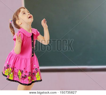 Pensive little girl with pigtails on the head , in a pink dress. The girl was looking at the top turned sideways to the camera.On a background of green, the school Board.