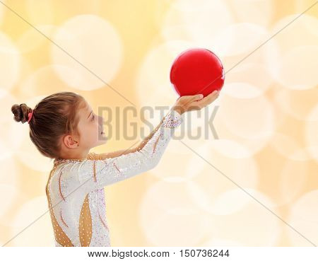 Cute little girl gymnast turned sideways to the camera , holding in his outstretched hands a red ball.On blurred brown background with white Christmas snowflakes.