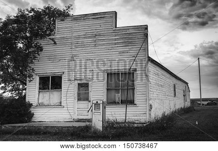 horizontal  black and white image of a very old wooden  abandoned store with one old vintage broken gas pump in the summer time.
