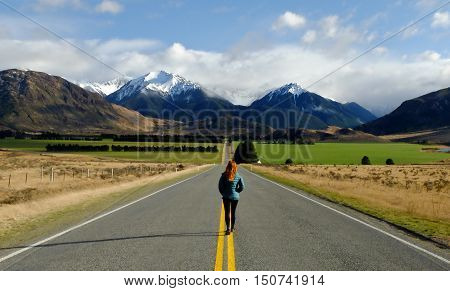 A Woman Walking the Long Road to Green Pastures and The Southern Alps.  Arthurs Pass National Park, Canterbury, New Zealand