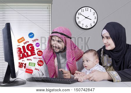 Happy middle eastern family using computer for shopping online with big sale and discount while looking at the computer and sitting in the office