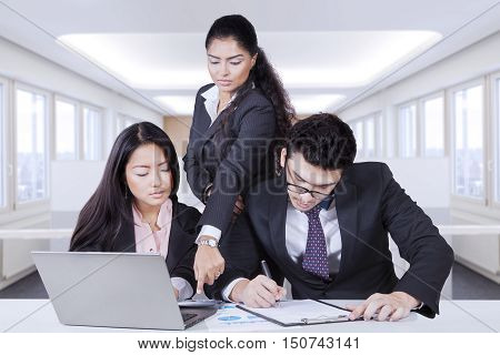 Image of two employee sitting and working serious while leader pointing mistake of counting in the calculator with laptop and clipboard on the table