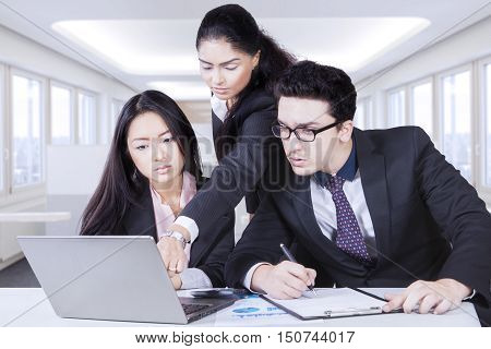 Image of woman leader pointing at laptop while her employees listening to the direction of the leader and looking at the laptop in the office