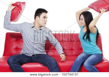 Young couple sitting and fighting on the red couch while they holding red pillows isolated on the white background