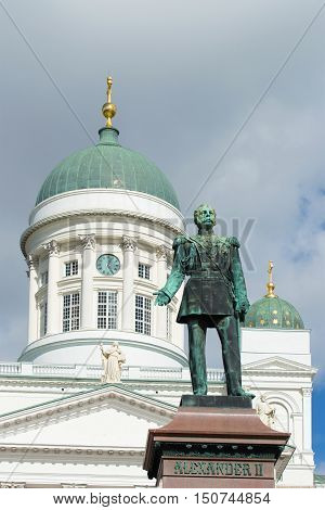 Sculpture of the Russian Emperor Alexander II (1894) on background of the dome of St. Nicholas Cathedral on a cloudy day. Helsinki, Finland