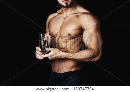 inflated healthy young man , holding a glass of water . A healthy way of life . On a dark background .