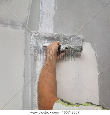 Worker Spreading Plaster To Wall