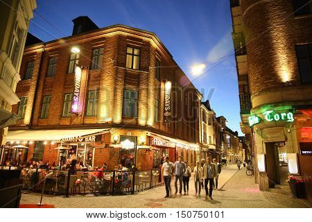 MALMO SWEDEN - AUGUST 16 2016: People walk on crossroad of the streets Master Johansgatan Lilla Torg and Landbygatan street in old part of Malmo street life in Malmo Sweden on August 16 2016.