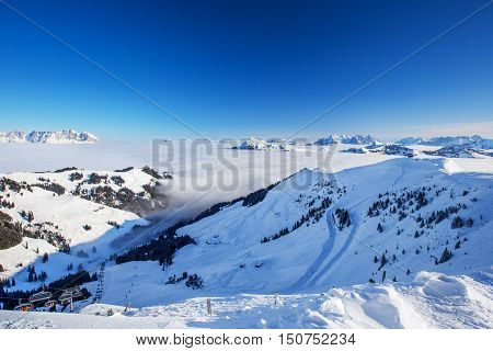 View To Alpine Mountains Surrounded By Fog And Ski Slopes In Austria From Kitzbuehel Ski Resort With