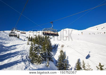 KITZBUEHEL AUSTRIA February 18 2016 - Skiers on ski lift enjoying the view to foggy Alps in Austria and beautiful snowy country panorama in famous Kitzbuehel mountain ski resort