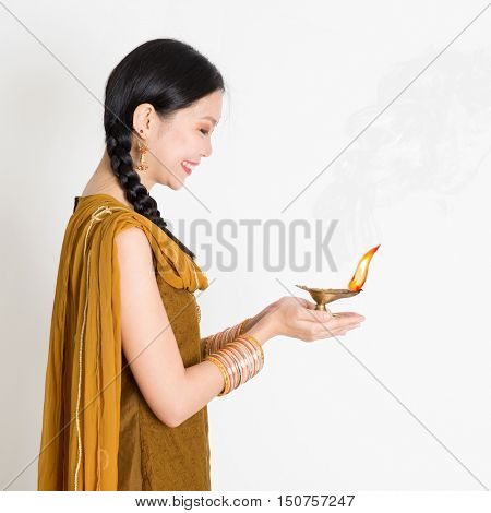 Profile view young mixed race Indian Chinese female in traditional dress hands holding diya oil lamp and celebrating Diwali or deepavali, fesitval of lights.