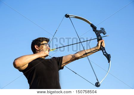 An archer drawing his compound bow in a field in the forest during the early autumn. Against the clear blue sky in October.
