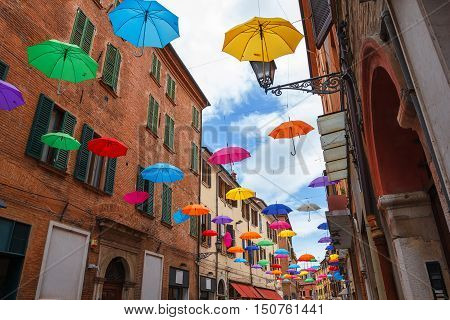 Colorful umbrellas hanging above street of Ferrara Italy