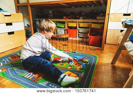 Cute little boy playing alone on toy carpet in his room at home
