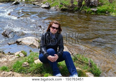 Girl in a black leather jacket sitting on the river bank with his hands crossed on her lap