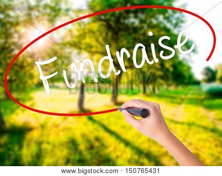 Woman Hand Writing Fundraise With A Marker Over Transparent Board