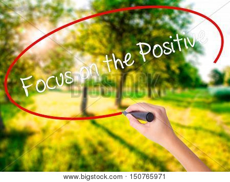 Woman Hand Writing Focus On The Positive With A Marker Over Transparent Board
