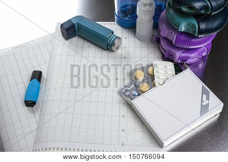 Asthma allergy illness relief concept salbutamol inhalers aerosol medication drugs and paper on chrome background