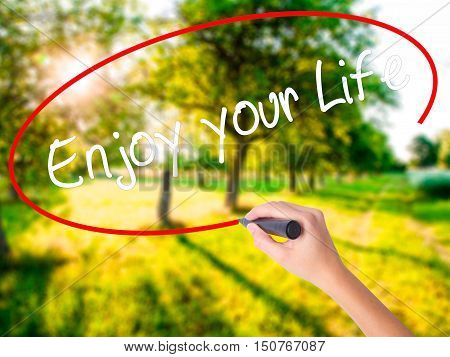 Woman Hand Writing Enjoy Your Life With A Marker Over Transparent Board