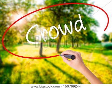 Woman Hand Writing Crowd With A Marker Over Transparent Board