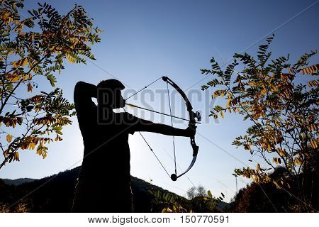 An archer drawing his compound bow in a field in the forest during the early autumn. A silhouette against the clear blue sky in October.
