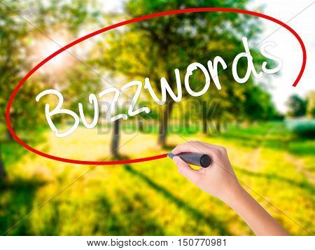 Woman Hand Writing Buzzwords With A Marker Over Transparent Board