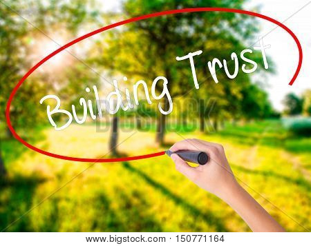 Woman Hand Writing Building Trust With A Marker Over Transparent Board