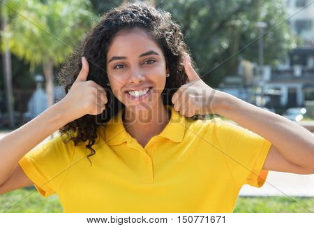 Beautiful latin american girl with long dark hair showing both thumbs outdoors in the summer in the city