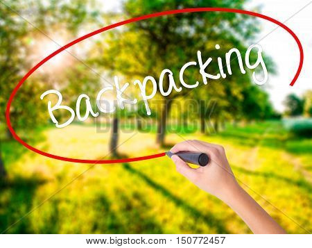 Woman Hand Writing Backpacking  With A Marker Over Transparent Board